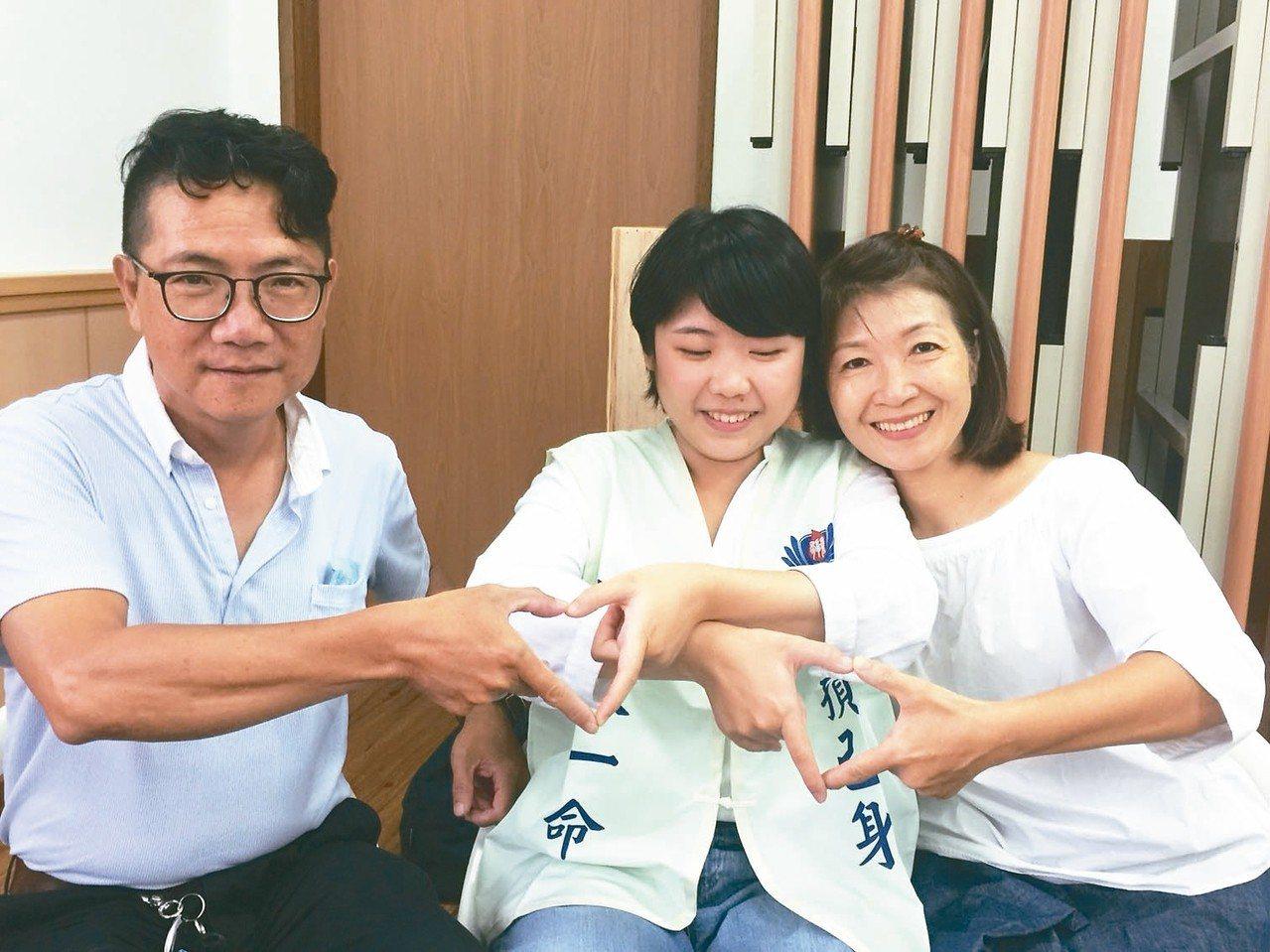 許家甄(中)與父親許清德(左)、母親謝美麗(右),拍照擺出心心相連手勢。 記者吳...
