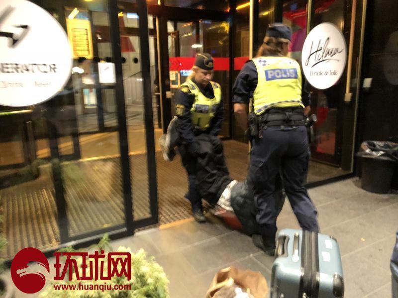 瑞典警察將陸客拖出旅店扔在地上,之後將其帶上警車。圖擷自環球網