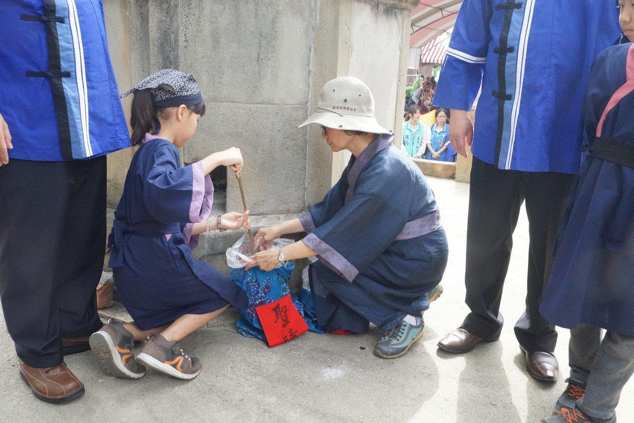 參與活動的小朋友將「聖蹟」裝入聖蹟袋中準備參加儀式。圖/桃園市客家事務局提供