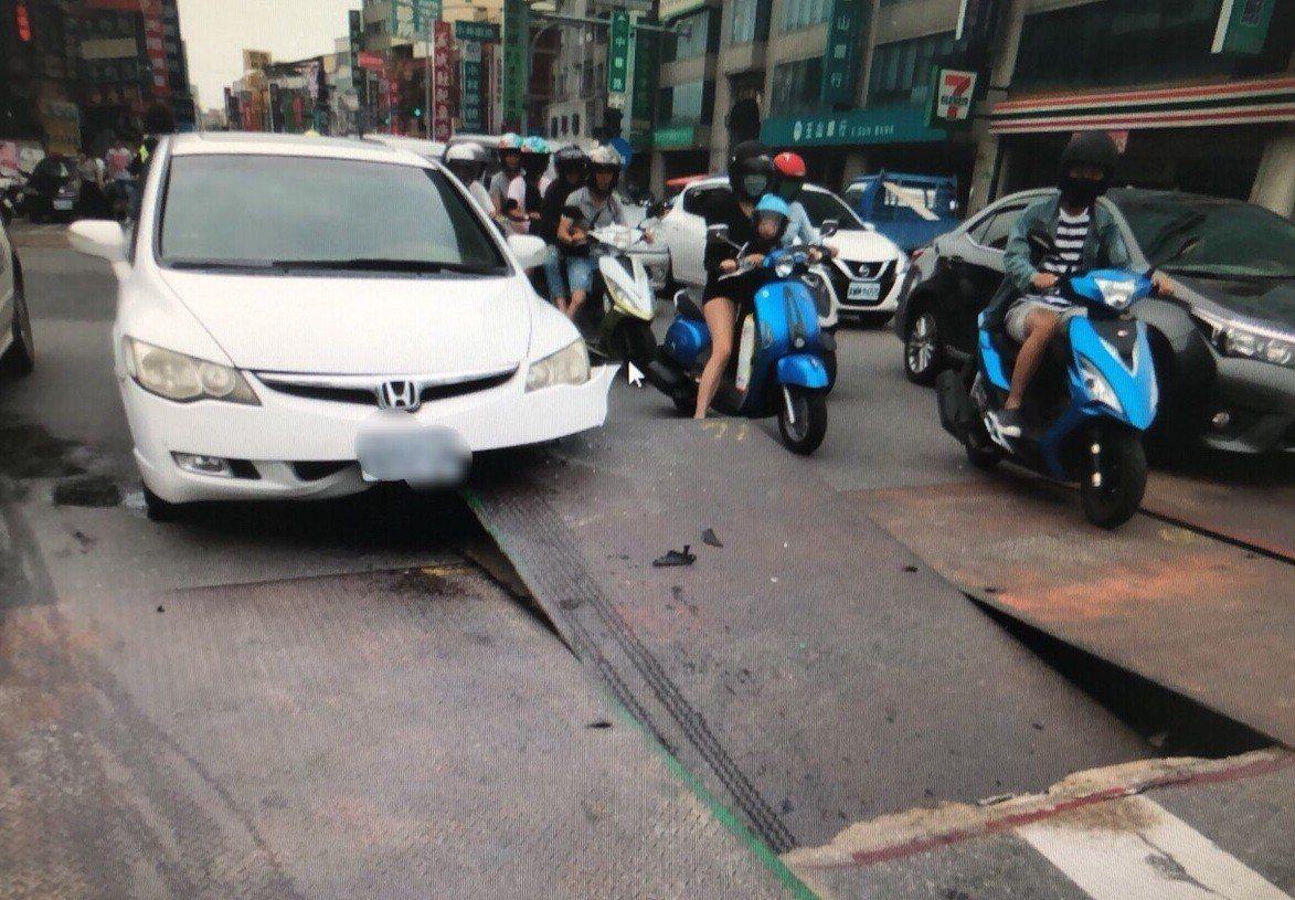 白色轎車行經永康區中華一路,被突然翹起鐵板撞擊,車頭受損。記者黃宣翰/翻攝