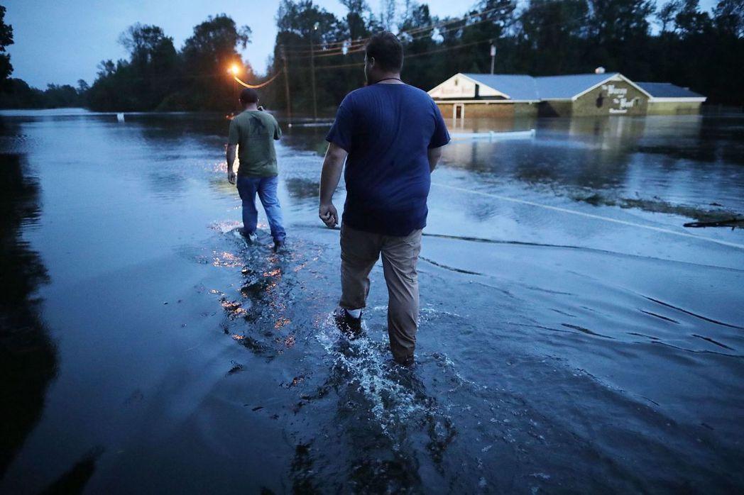 美國北卡州金斯頓市嚴重積水,志工15日晚涉水協助救災。 (法新社)