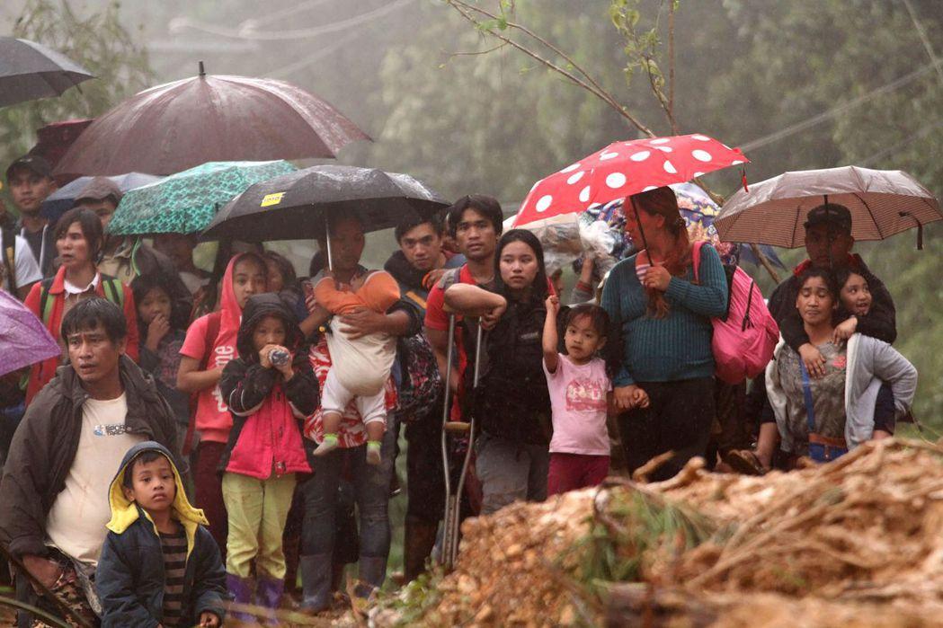菲律賓本格特省發生山崩與活埋後,礦工的親人16日撤往安全處。 (法新社)