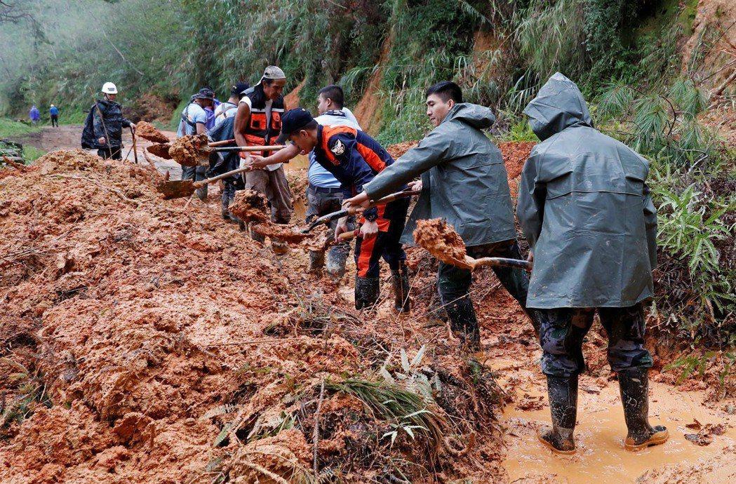 警察與消防人員16日在菲律賓本格特省波科鎮,清理颱風山竹造成的坍方。 (路透)