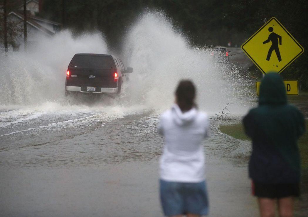 美國北卡州威明頓市16日因佛羅倫斯颶風嚴重淹水,一輛車行經水深處時,激起強大水花...