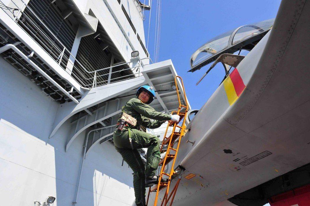 大陸艦載機飛行員駕駛國產殲—15艦載戰鬥機在遼寧艦上進行阻攔著艦和滑躍起飛。圖為...