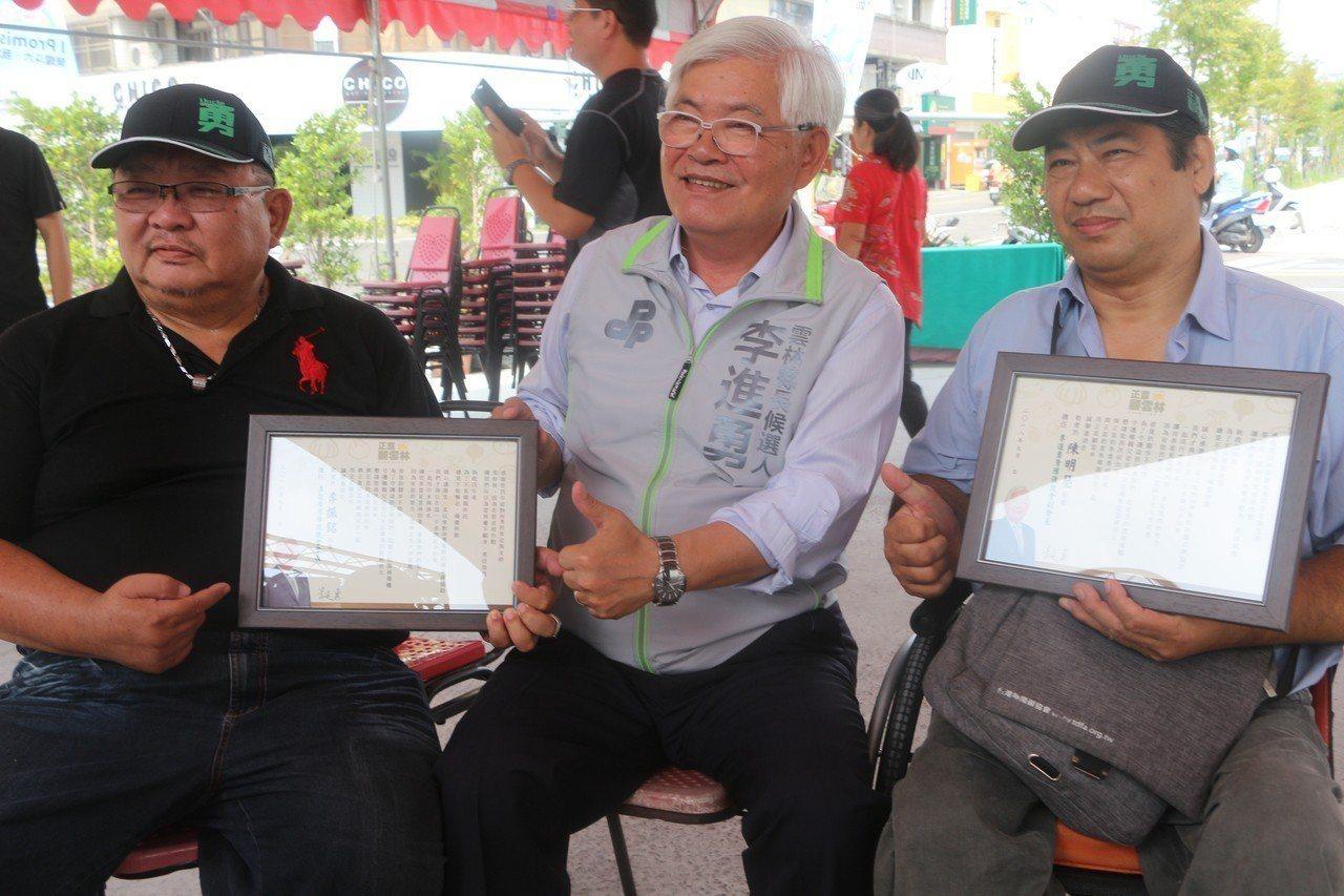 身心障礙後援會長李振銘(左)致贈感謝狀給李進勇(中),感謝他四年來的努力,李進勇...