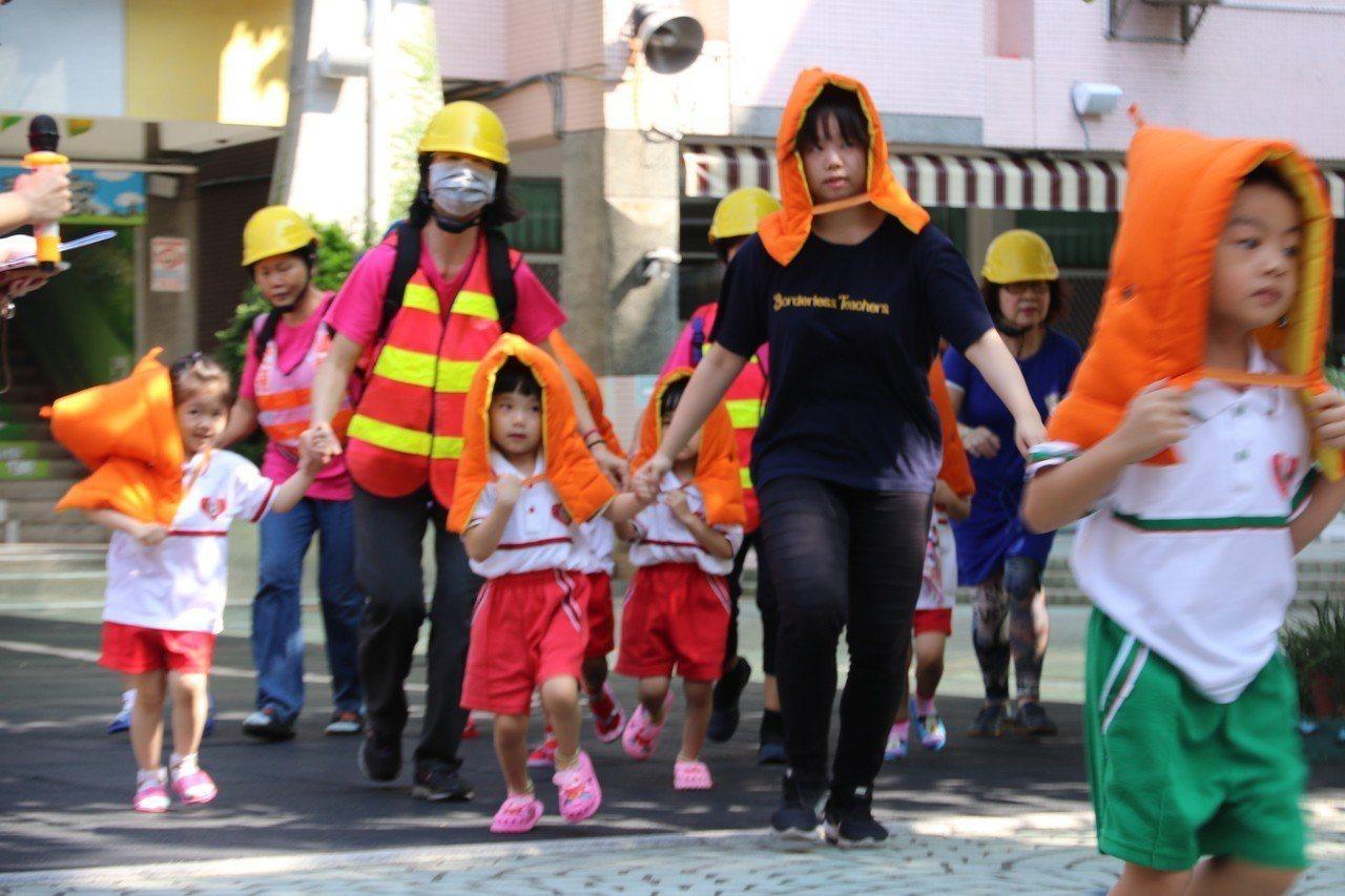 前金幼兒園進行地震避難疏散演練,小朋友聽從師長指揮,迅速離開建築物至空曠地。記者...