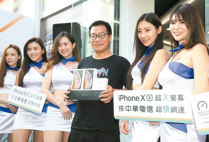 iPhone XS系列開賣,中華電信搶頭香的果粉Mike(右三)開心拿著戰利品與model合照。 記者余承翰/攝影
