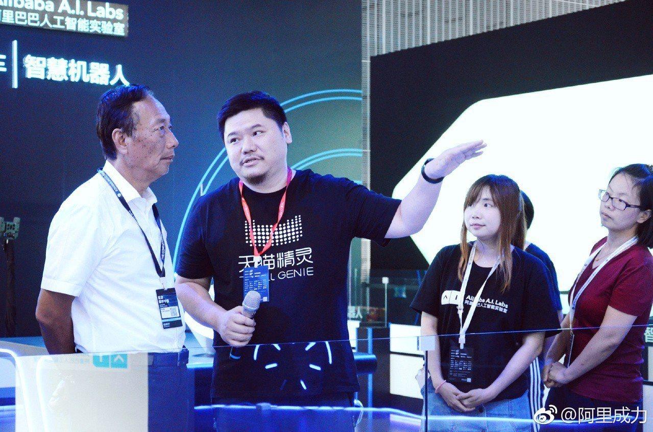 鴻海集團董事長郭台銘聽取阿里最新的服務機器人和智慧物流車介紹。取自/阿里成力微博