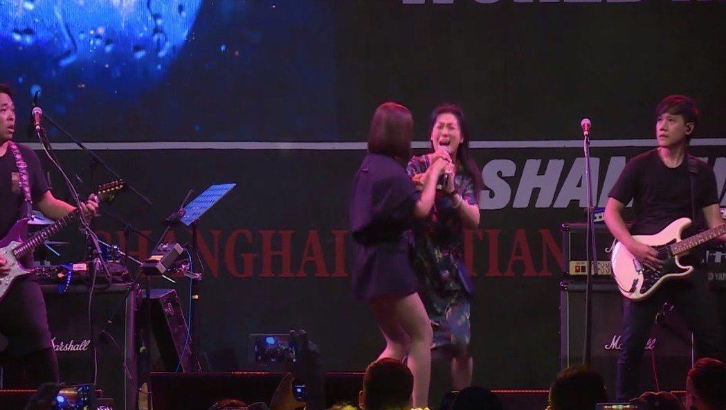 丁噹(左)唱到一半,麥克風被衝上台的婦人搶走。圖/摘自臉書