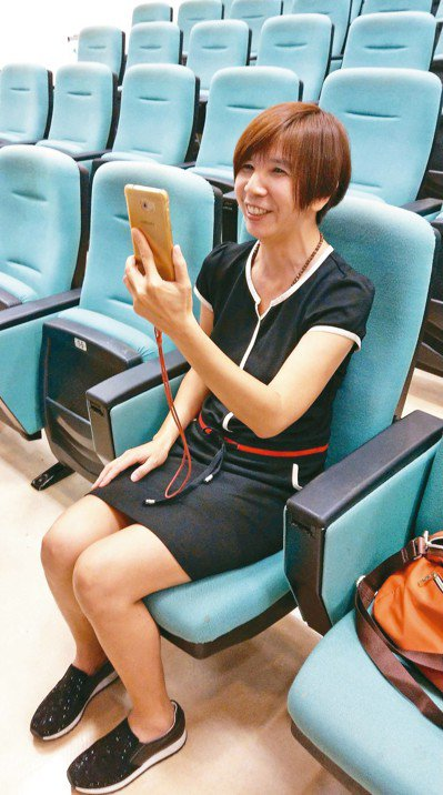 何姓美容院老闆娘示範正確看手機姿勢。 記者趙容萱/攝影
