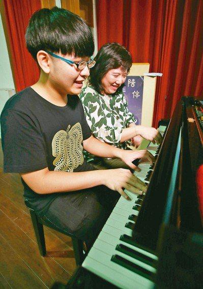 總統教育獎推手陳蔚綺老師(右)與他的學生陳彥豪(左)一同彈奏鋼琴。 記者杜建重/...