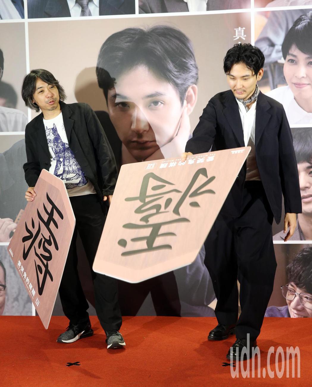 松田龍平(右)、豐田利晃(左)來台為電影「愛哭鬼的棋蹟」作宣傳,兩人拿著大型的將...