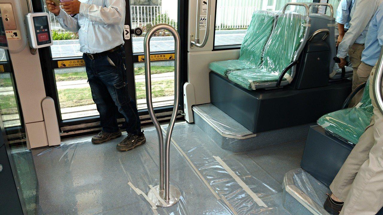 高雄輕軌二階列車的中間扶桿,高度只到半身,方便民眾手扶,也讓車內視野更開闊。記者...