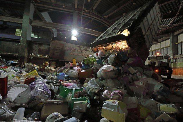 在台北市,每天資源回收項目不同,民眾必須依規定分類丟棄。但《天下》直擊,資收車回到北區回收場後,扣除廢紙,包含鋁罐、塑膠、寶特瓶、小家電、玻璃瓶、紙容器等,全部混雜卸下,等屏東回收業者開車先北上再南下,運回給屏東工人重新分類,這不是「欺騙」民眾做分類白工嗎? 圖片來源:王建棟攝