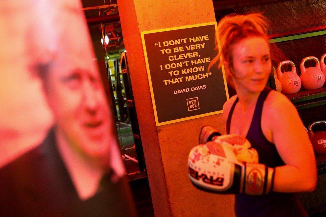 學員出拳去揍印有強生肖像的沙包,牆上貼著英國前脫歐事務大臣戴維斯的語錄:「我沒必...