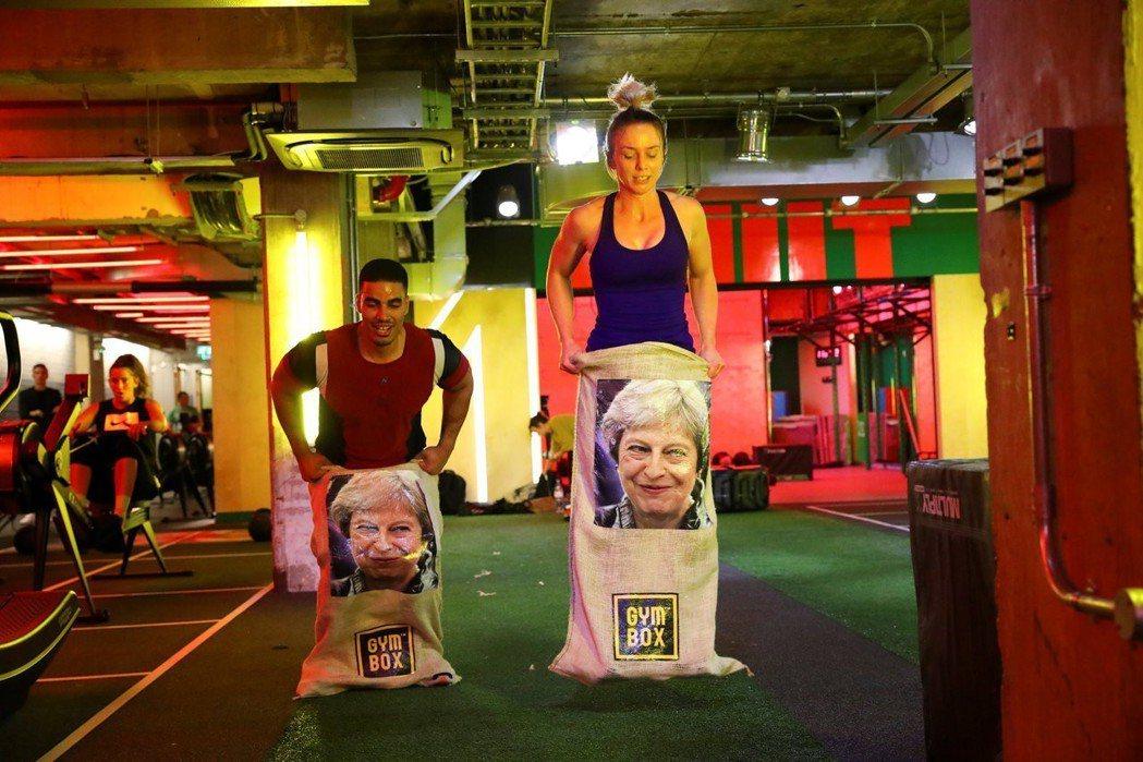健身房學員腳上套著印有梅伊肖像的布袋跳躍。 (路透)