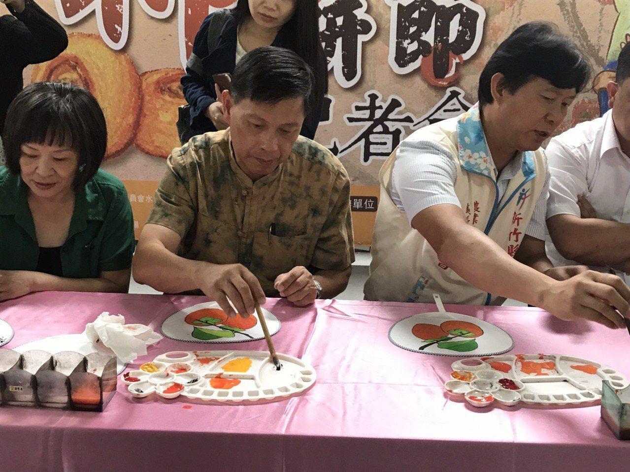 新埔鎮農會昨天在金漢柿餅教育園區舉辦行前記者會,現場來賓用水彩在扇子上一起畫「柿...