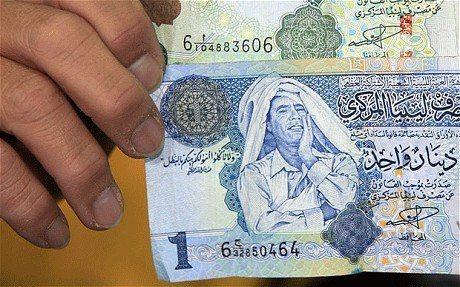 印有格達費畫面的利比亞貨幣第納爾。(歐新社)