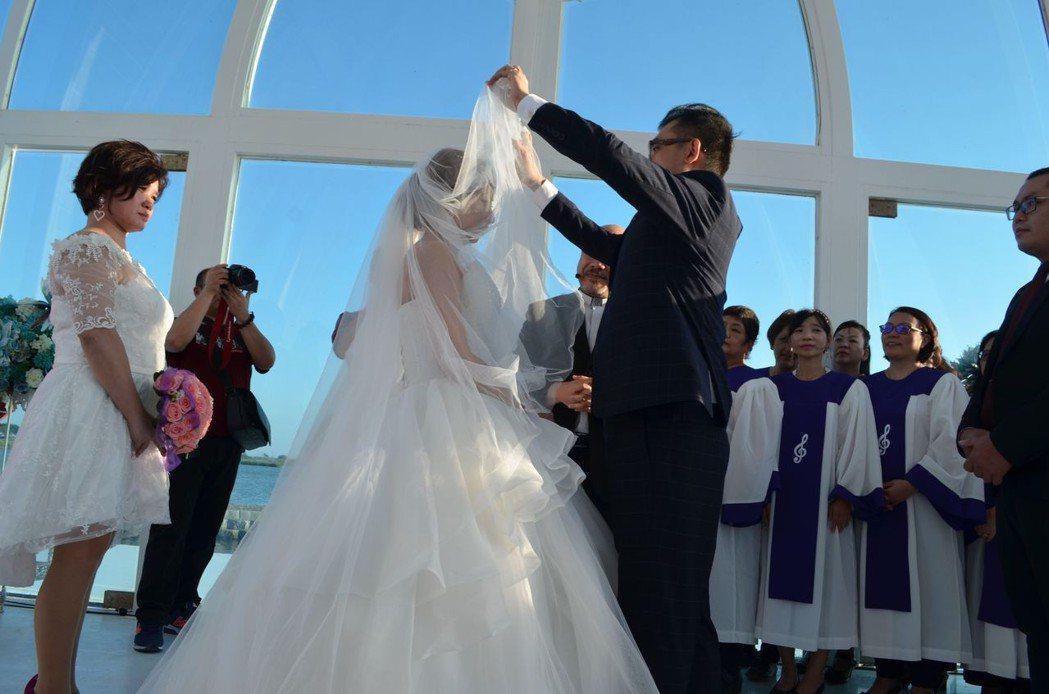 新郎為新娘掀開頭紗。  陳慧明 攝影