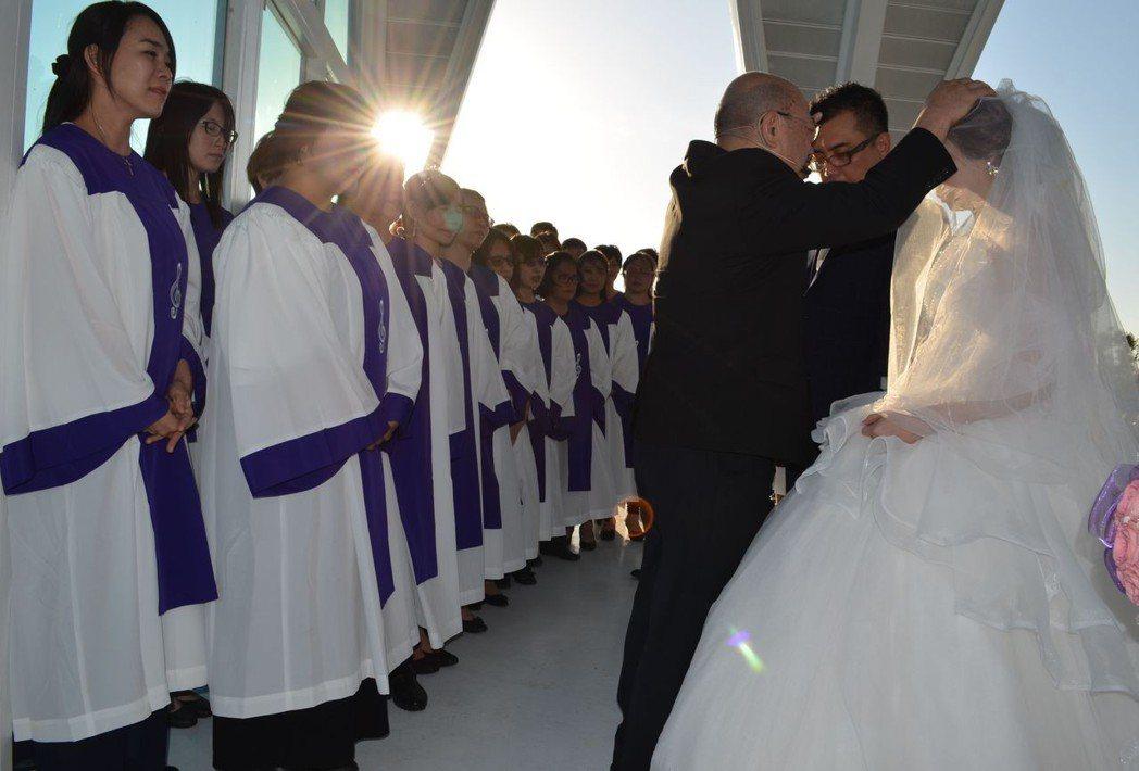 主禮牧師吳文朗為新人祝禱。  陳慧明 攝影