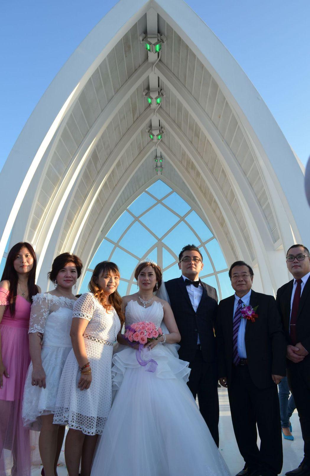完婚後,新人與主婚人廖峻及伴郎伴娘在水晶教堂前合影。  陳慧明 攝影