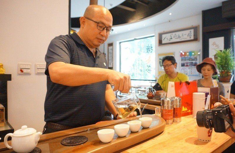 「楊館主」楊國珍以桂花烏龍茶包泡茶,邀來客試飲。 徐谷楨/攝影