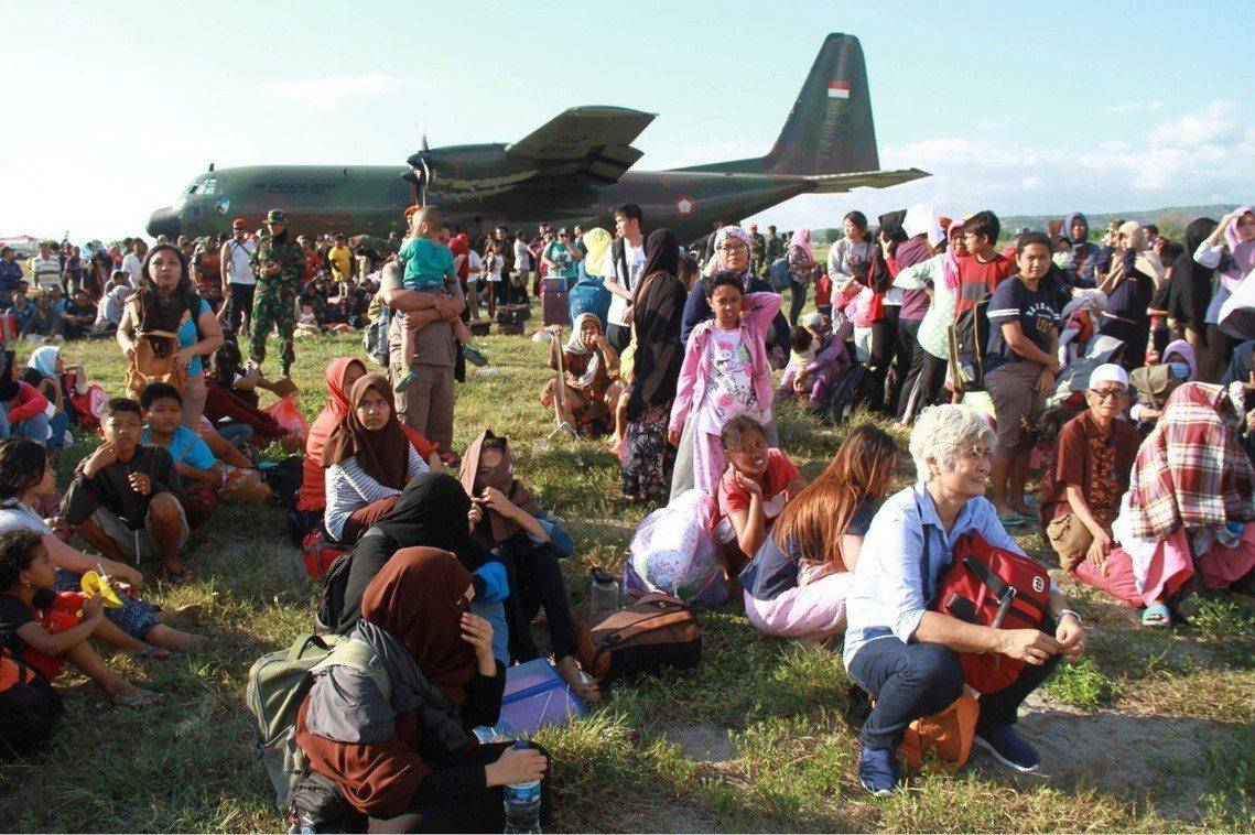 衝進機場裡希望和C-130一起走的大批災民。 圖/路透社