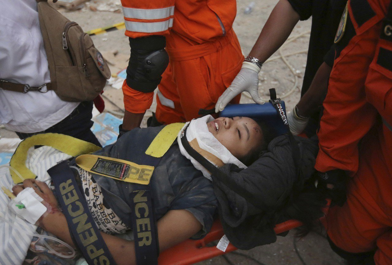 搜救人員9月30日在一間倒塌的餐廳內救出一名生還者。美聯社