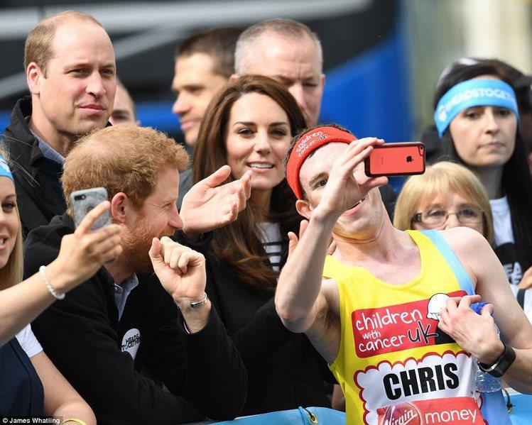 2017年的倫敦馬拉松,一名跑者停下來和在旁邊加油的威廉、凱特和哈利王子自拍。圖...