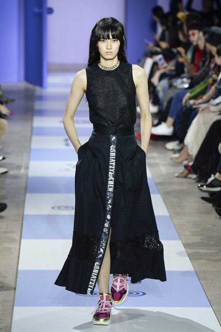 高衩長裙、大衣領口邊緣也用印有SHIATZY CHEN和甲蟲、時鐘等圖案的塗鴉感...