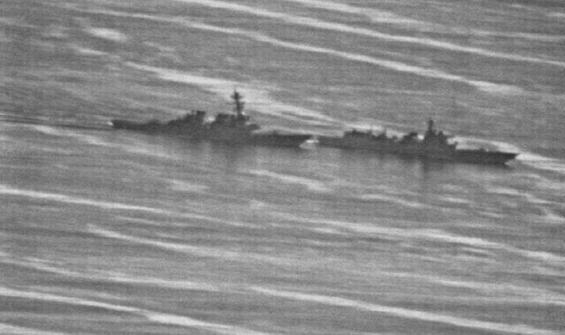 美海軍公布的偵察照片顯示,美「狄卡特號」導彈驅逐艦(左),日前在南沙群島南薰礁1...
