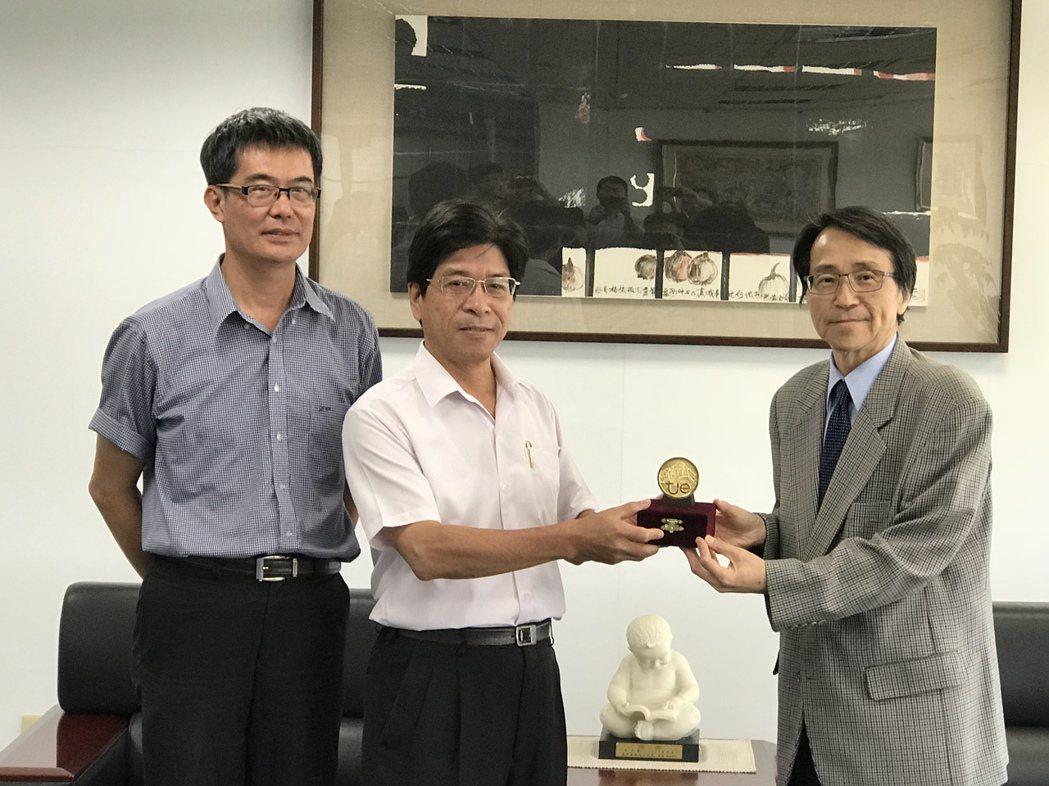 嘉南藥理大學副校長杜平悳(左二)將金牌獎獻給校長陳鴻助(右)。 黃逢森/攝影