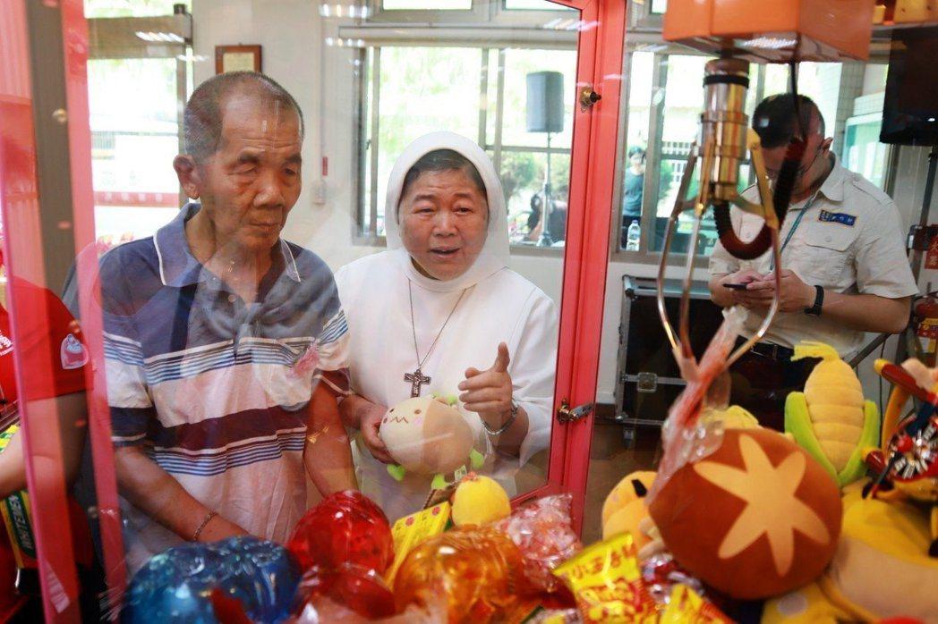 中華聖母基金會首次設置「夾娃娃機」,基金會董事長陳美惠(右)指導阿公玩,也達到手...