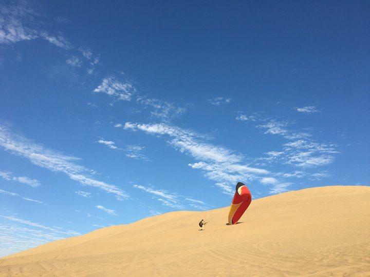白晝的沙漠(4)-飛行傘在沙漠撐開的模樣。 圖/背包客棧
