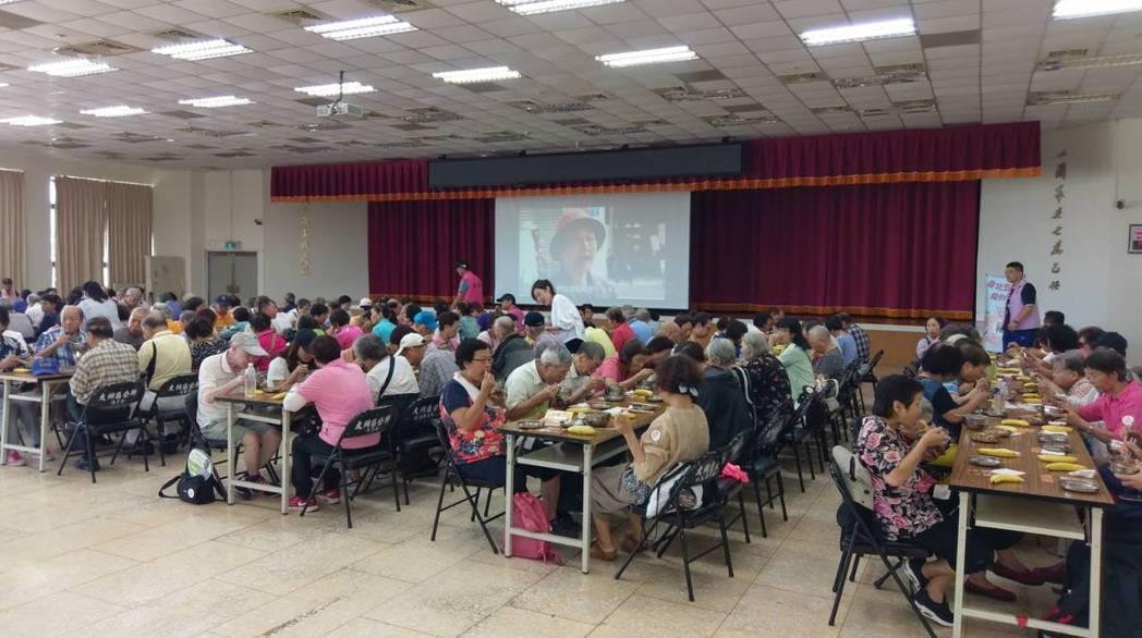 參加台北市政府「長青樂活遊台北」1日遊的長者,中午被安排在區公所大禮堂用餐。圖/...