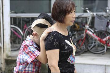 出門只敢躲在媽媽的背後,無法面對人群。圖擷自騰訊新聞網