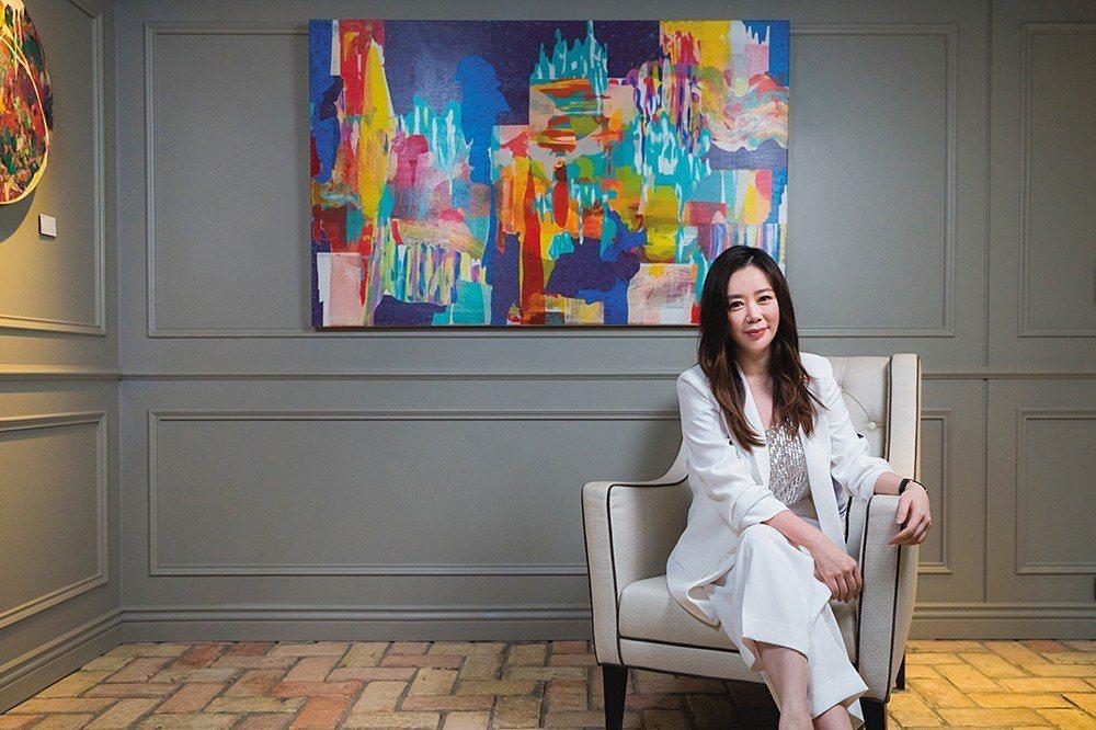 江欣宜在繽紛設計的辦公室接受訪問。美麗的空間中,最好的展牆放著藝術家何政宏的壓克...