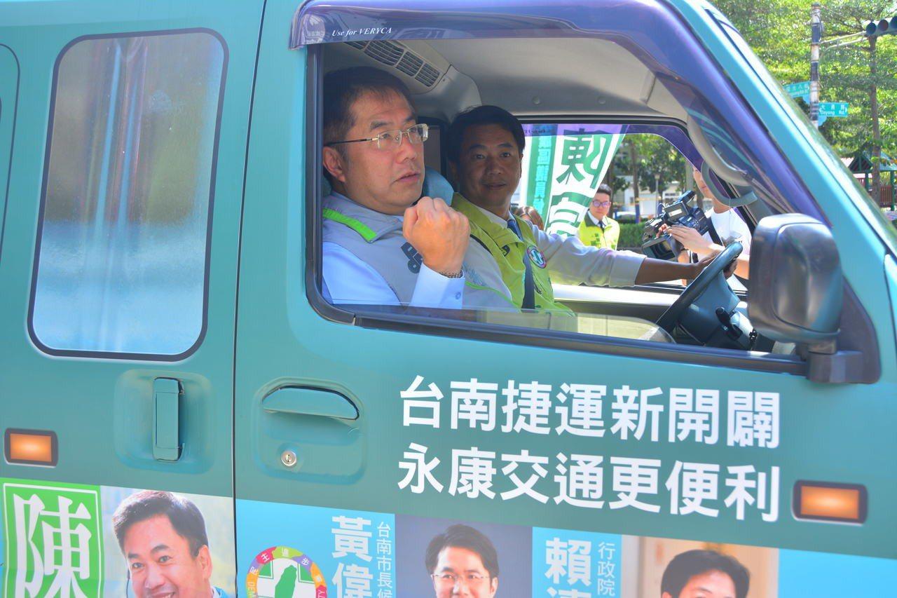 民進黨台南市長參選人黃偉哲(左)與市議員參選人陳宗明(右)開著台南捷運概念車上路...