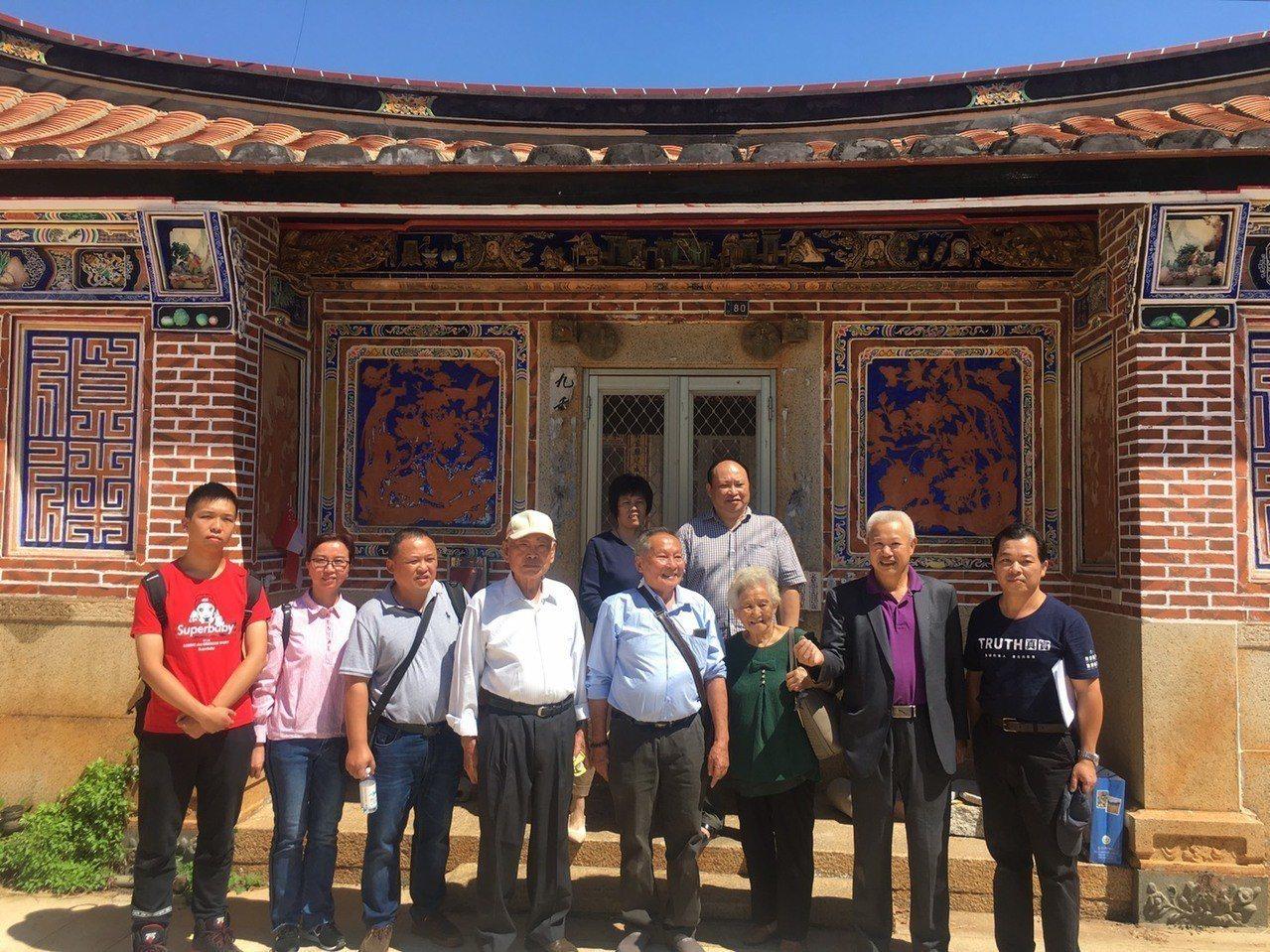 祖籍在金門盤山的80歲老人翁卓慶(右四)帶著家人回到故鄉尋根,並在以前的老宅前合...