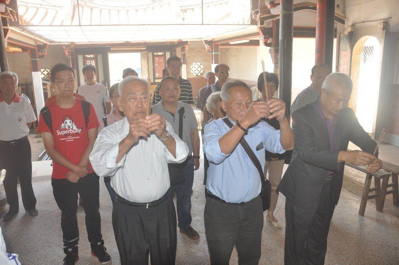 今年80歲的出洋客翁卓慶(中)帶著家人回到故鄉尋根,並到翁氏宗祠上香合影。 記者...