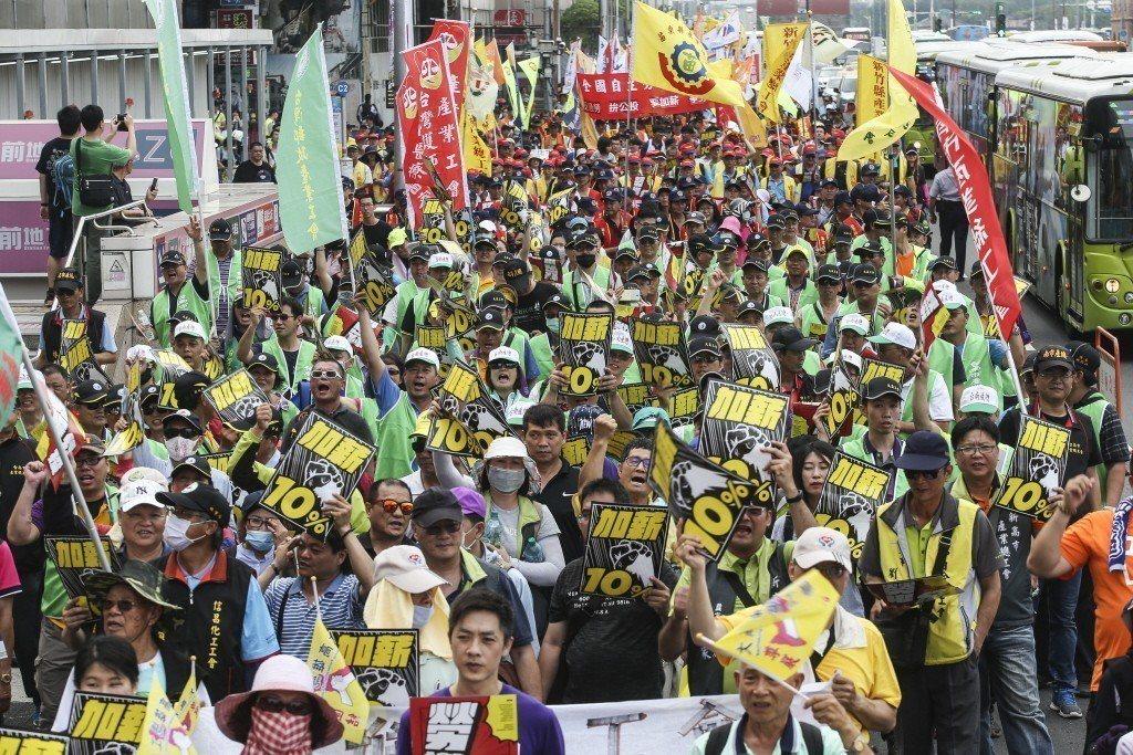 今年五一勞動節號萬人上街,高舉四大標語「反過勞!拼公投!要加薪!爭勞權!」。 圖...