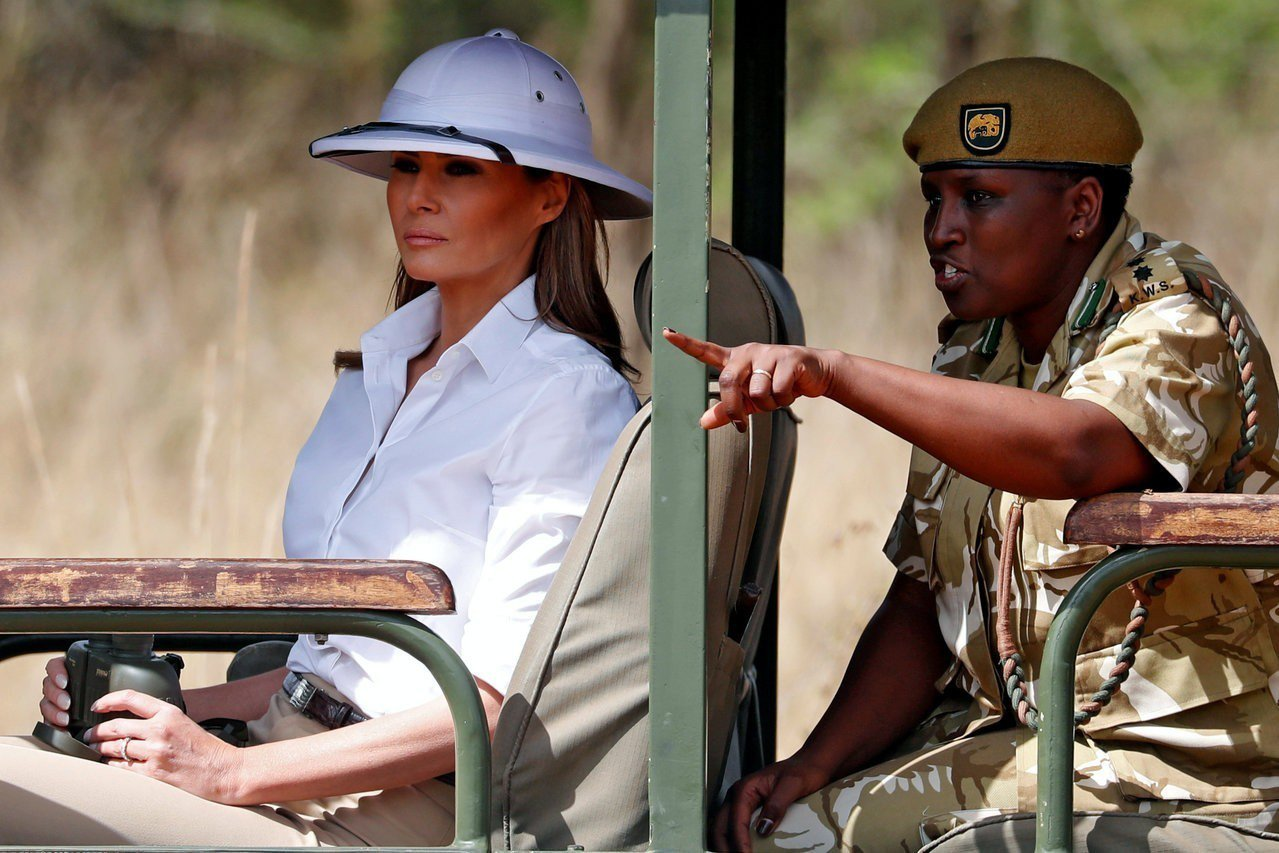 美國第一夫人梅蘭妮亞(左)5日前往肯亞奈洛比國家公園觀光,頭上戴的白色遮陽帽引起...