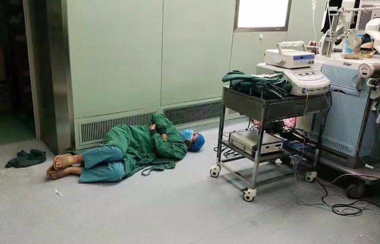 醫生做24小时手術後太累,睡地板上。圖取自新浪網