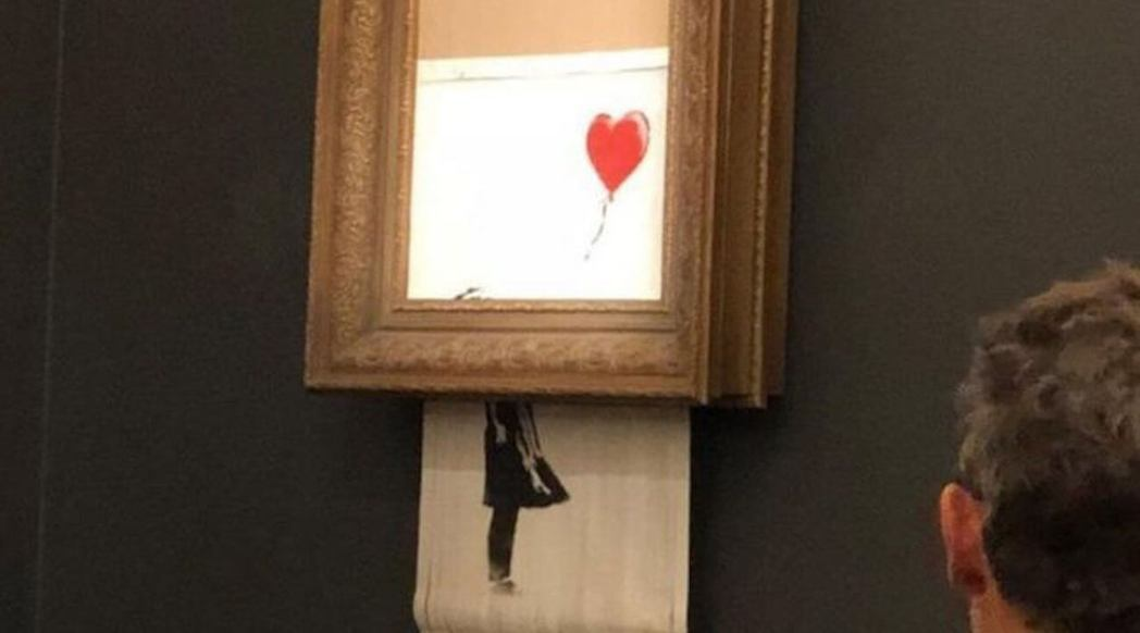 「汽球女孩」的半幅畫被碎成條狀並滑出框外。 圖/取自網路