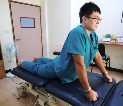 預防腰椎椎間盤突出第二招「腰部伸直運動」,俯臥在床面,手握拳置於肩關節下方,手肘...