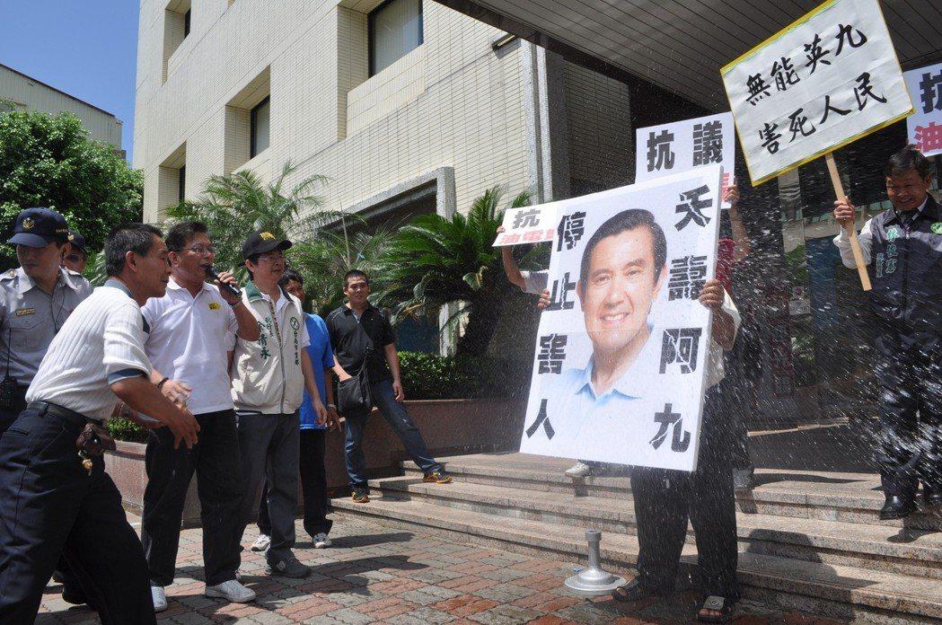 不滿馬政府調漲電價,民進黨支持者向馬英九肖像砸水球抗議。圖╱聯合報系資料照片