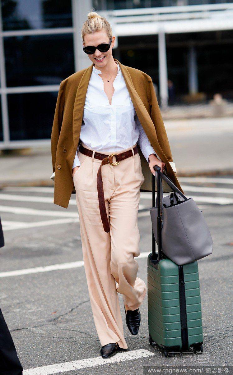 超模KK的亮褐色外套為素雅穿搭提升明亮感。圖/達志影像