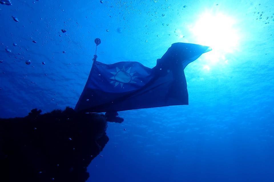 將國旗綁上浮球跟鉛塊就能水中順利張開,隨著海流飄揚。圖/李益利提供