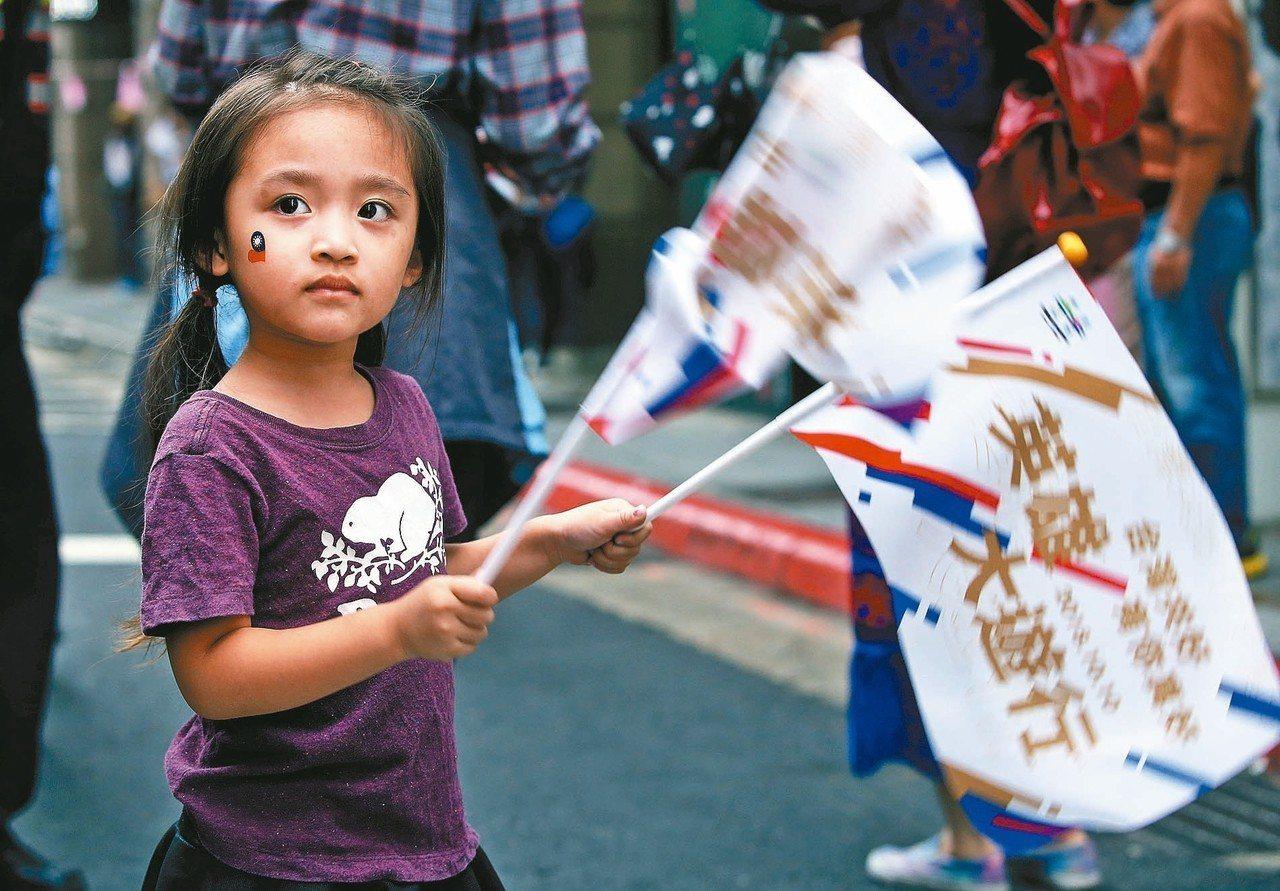 雅加達亞運國手在國慶日遊街,有小朋友舉著旗幟開心舞動,迎接台灣英雄。 記者陳柏亨...